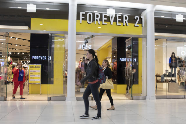 People walk in front of a Forever 21 clothing store, Monday, Sept. 30, 2019, in New York. Low-price fashion chain Forever 21, a one-time hot destination for teen shoppers that fell victim to its own rapid expansion and changing consumer tastes, has filed for Chapter 11 bankruptcy protection. (AP Photo/Mark Lennihan)