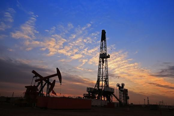 A drilling rig near some oil pumps with a nice sunset in the background.