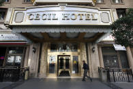 A visitor arrives at the hotel Cecil on Wednesday Feb. 20,2013 where police say the body of a woman was found wedged in one of the water tanks on the roof was that of a missing Canadian guest. Investigators used body markings to identify 21-year-old Elisa Lam, police spokeswoman Officer Diana Figueroa said late Tuesday. A maintenance worker at the Cecil Hotel found the body earlier in the day after guests complained of low water pressure. (AP Photo/Nick Ut)