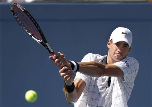 John Isner returns a shot to Xavier Malisse of Belgium in the second round of play at the 2012 US Open tennis tournament, Wednesday, Aug. 29, 2012, in New York. (AP Photo/Mel C. Evans)