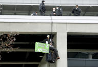 An activist hangs on an airport building to protest against the opening of the new Berlin-Brandenburg-Airport 'Willy Brandt' in Berlin, Germany, Saturday, Oct. 31, 2020. Berlin's new airport opens after years of delays and cost overruns. (AP Photo/Michael Sohn)