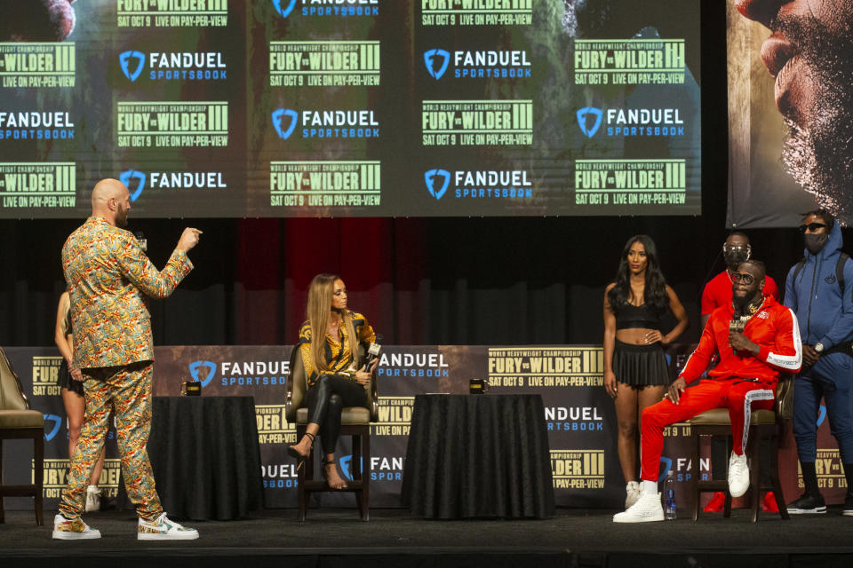 Tyson Fury, left, and Deontay Wilder, seated, in reed, participate during a news conference in advance of their heavyweight title boxing bout, in Las Vegas on Wednesday, Oct. 6, 2021. (Erik Verduzco/Las Vegas Review-Journal via AP)