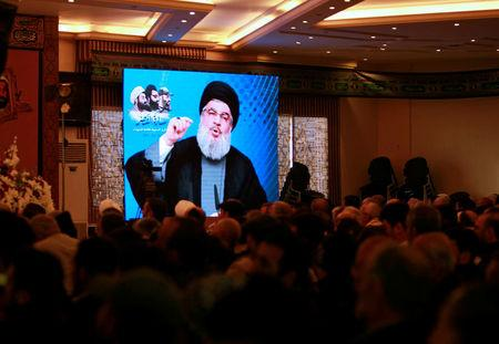 Lebanon's Hezbollah leader Sayyed Hassan Nasrallah addresses his supporters through a screen during a rally commemorating the annual Hezbollah Martyrs' Leaders Day in Jebshit village