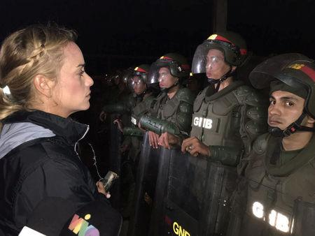 Lilian Tintori (L), wife of jailed Venezuelan opposition leader Leopoldo Lopez, stands in front of Venezuelan National Guards looking for information about her husband outside the military prison of Ramo Verde, in Los Teques, Venezuela May 4, 2017. Prensa Lilian Tintori/Handout via REUTERS