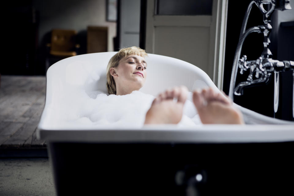 Blond woman taking bubble bath in a loft