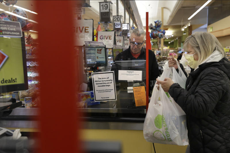 Cashier George Wallace, of Quincy, Mass., center, works behind a plastic shield as a shopper, right, places groceries in a cart, Thursday, March 26, 2020, at a grocery store, in Quincy. Grocery stores across the U.S. are installing protective plastic shields at checkouts to help keep cashiers and shoppers from infecting each other with the coronavirus.  (AP Photo/Steven Senne)