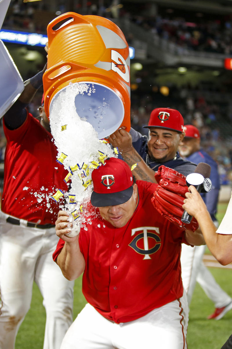 Minnesota Twins starting pitcher Bartolo Colon is doused by teammates after throwing a complete baseball game against the Rangers. (AP)