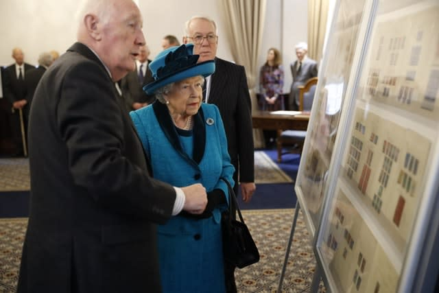 The Queen is shown stamps of previous British monarchs during a visit to the new headquarters of the Royal Philatelic Society