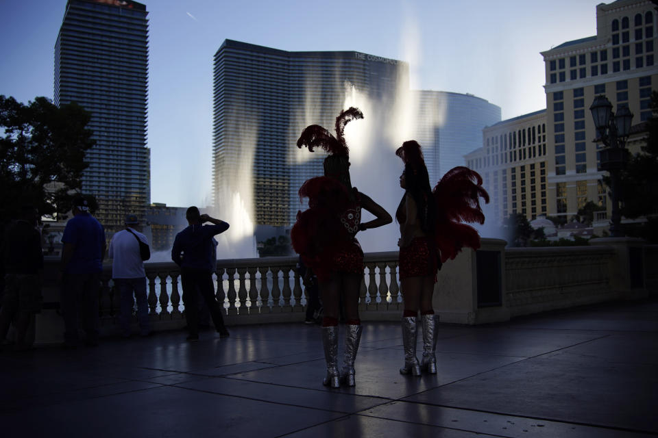 FILE - In this Nov. 19, 2020, file photo, people dressed as showgirls stand along the Las Vegas Strip in Las Vegas. Two prominent Las Vegas communications executives are suing more than 20 online travel companies for back taxes they say should have been paid to Nevada based on hotel room rates. (AP Photo/John Locher, File)