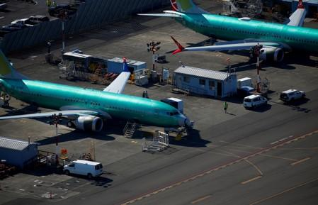 FILE PHOTO: A worker walks past unpainted Boeing 737 MAX aircraft parked at Renton Municipal Airport in Renton