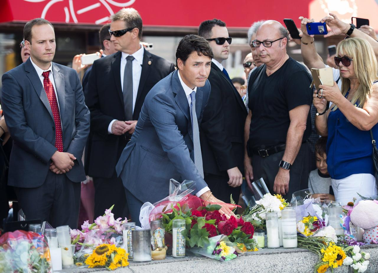 <p>Prime Minister Justin Trudeau places flowers at the fountain at the Alexander the Great Parkette, near where people were gunned down and injured from the recent Danforth shootings in Toronto on Monday, July 30, 2018. Photo from The Canadian Press. </p>