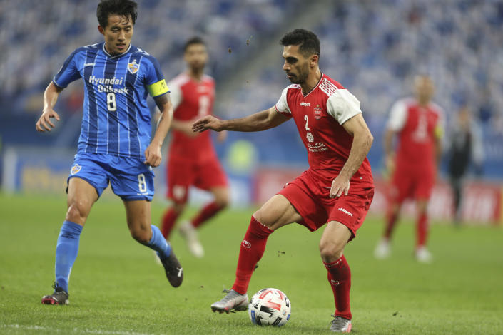 Ulsan Hyundai's Sin Jin-Ho, left, and Amir Roustaei of Persepolis fight for the ball during the AFC Champions League final match in Al Wakrah, Qatar, Saturday, Dec. 19, 2020. (AP Photo/Hussein Sayed)