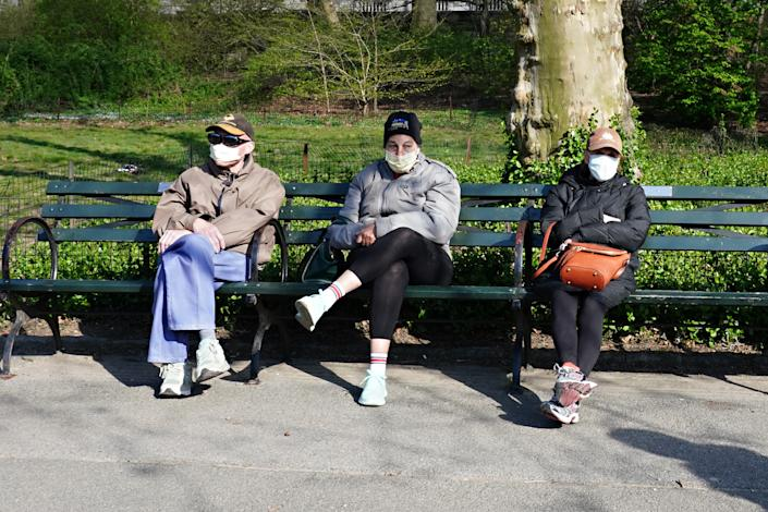 New Yorkers heed advice to wear masks to help control the spread of the coronavirus as they sit in Central Park in New York City on April 11, 2020. | Cindy Ord—Getty Images