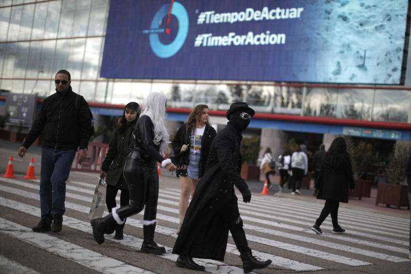 People walk outside of the COP25 climate talks congress in Madrid, Spain, Saturday, Dec. 14, 2019. The United Nations Secretary-General has warned that failure to tackle global warming could result in economic disaster. (AP Photo/Manu Fernandez)
