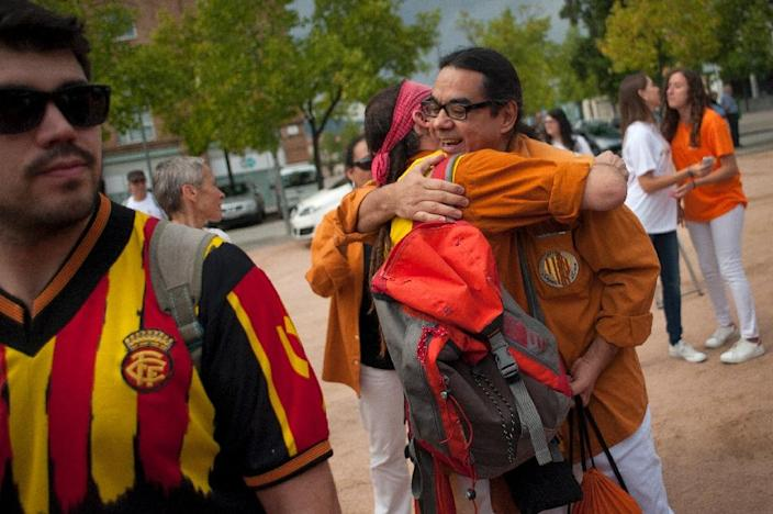 Venezuelan Wilmer Gonzalez (R) embraces a friend on a square in Vic a few hours before celebrations for Catalonia's National Day on September 11, 2015 (AFP Photo/Jorge Guerrero)