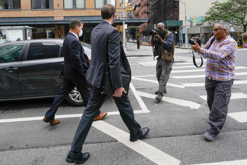Photographers surround federal agents as they leave the building that houses the Sergeants Benevolent Association offices, Tuesday, Oct. 5, 2021, in New York. Federal agents raided the offices of a New York City police union whose leader has clashed with city officials over his incendiary tweets and hard-line tactics. They also raided the Long Island home of Sergeants Benevolent Association president Ed Mullins. (AP Photo/Mary Altaffer)