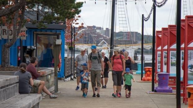 People stroll on a pier in Halifax back in September. The Atlantic bubble's success at containing COVID-19 in the region gave people more freedom to move about.