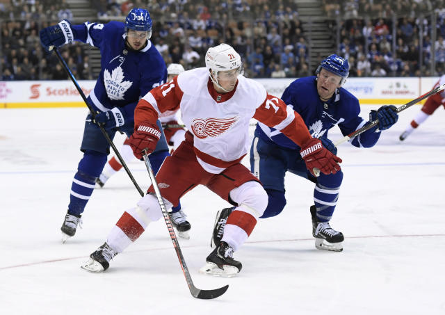 Detroit Red Wings center Dylan Larkin (71) moves past Toronto Maple Leafs defenseman Morgan Rielly (44) as Maple Leafs center Auston Matthews (34) watches during the third period of an NHL hockey game Thursday, Dec 6, 2018, in Toronto. (Nathan Denette/The Canadian Press via AP)