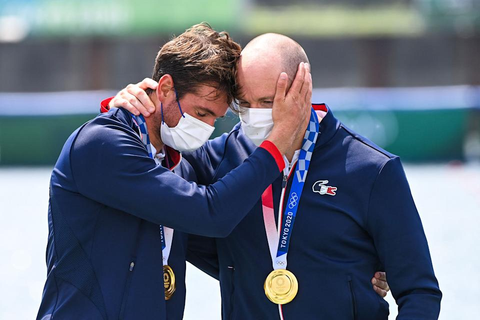 <p>Gold medallists France's Hugo Boucheron and Matthieu Androdias react on the podium following the men's double sculls final during the Tokyo 2020 Olympic Games at the Sea Forest Waterway in Tokyo on July 28, 2021. (Photo by Charly TRIBALLEAU / AFP)</p>