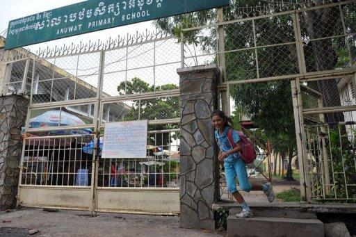 A Cambodian girl runs out of a school gate in Phnom Penh