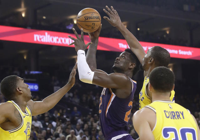 Phoenix Suns center Deandre Ayton, center, shoots between Golden State Warriors' Kevon Looney, left, Kevin Durant, top right, and Stephen Curry during the first half of an NBA basketball game in Oakland, Calif., Sunday, March 10, 2019. (AP Photo/Jeff Chiu)