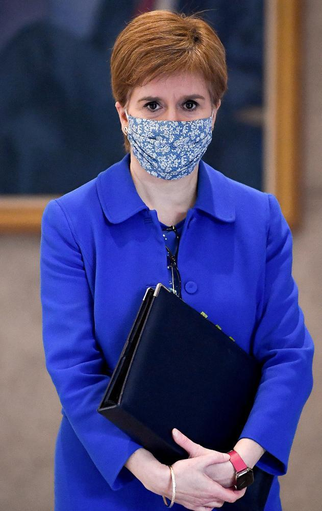 Nicola Sturgeon in a face mask holding a document folder