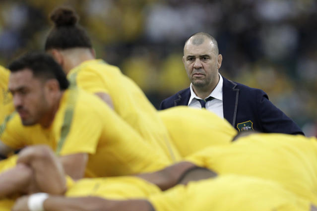Australia coach Michael Cheika watches as his team warm up before the Rugby World Cup quarterfinal match at Oita Stadium between England and Australia in Oita, Japan, Saturday, Oct. 19, 2019. (AP Photo/Aaron Favila)