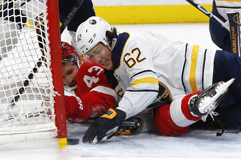 Buffalo Sabres defenseman Brandon Montour (62) pushes the puck from the goal as Detroit Red Wings left wing Darren Helm (43) looks on in the second period of an NHL hockey game Sunday, Jan. 12, 2020, in Detroit. (AP Photo/Paul Sancya)