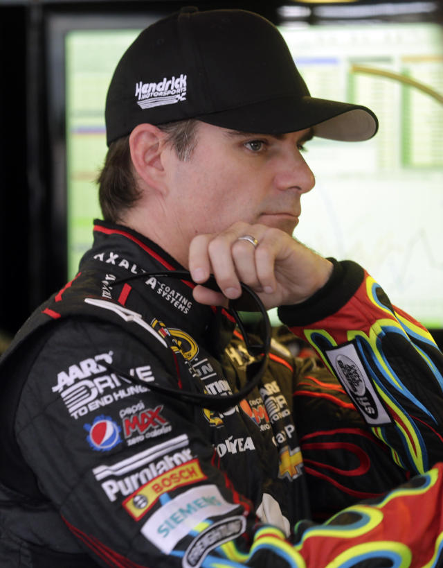 Driver Jeff Gordon watches in the garage area as his team works on his car during practice for Sunday's NASCAR Sprint Cup Series auto race at Talladega Superspeedway in Talladega, Ala., Friday, Oct. 18, 2013.(AP Photo/Jay Sailors)
