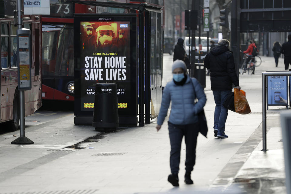 A coronavirus information sign is displayed by a bus stop in London, Friday, Jan. 15, 2021, during England's third national lockdown since the coronavirus outbreak began. The U.K. is under an indefinite national lockdown to curb the spread of the new variant, with nonessential shops, gyms and hairdressers closed, most people working from home and schools largely offering remote learning. (AP Photo/Matt Dunham)