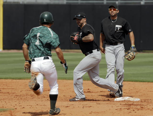 Major League Baseball free agent second baseman Tyler Ladendorf, center, and Omar Infante, right, team up to force JR East base runner Sato at second base and turn a double play on Hasagawa during an exhibition baseball game Tuesday, Feb. 27, 2018, in Bradenton, Fla. (AP Photo/Chris O'Meara)