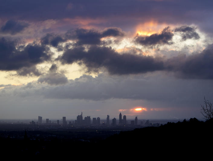 The sun rises between clouds over the banking district of Frankfurt, Germany, Tuesday, Jan. 8, 2019. (AP Photo/Michael Probst)