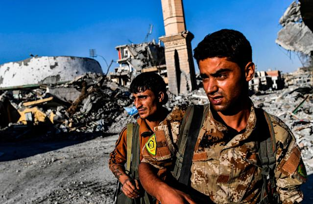 <p>Members of the Syrian Democratic Forces (SDF), backed by US special forces, check the area near Raqa's stadium as they clear the last positions on the frontline on Oct. 16, 2017 in the Islamic State (IS) group jihadists crumbling stronghold. (Photo: Bulent Kilic/AFP/Getty Images) </p>