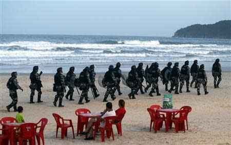 Riot police patrol the Santinho beach next the Costao do Santinho hotel ahead of the 2014 FIFA World Cup in Florianopolis, Santa Catarina state, February 19, 2014. REUTERS/Sergio Moraes