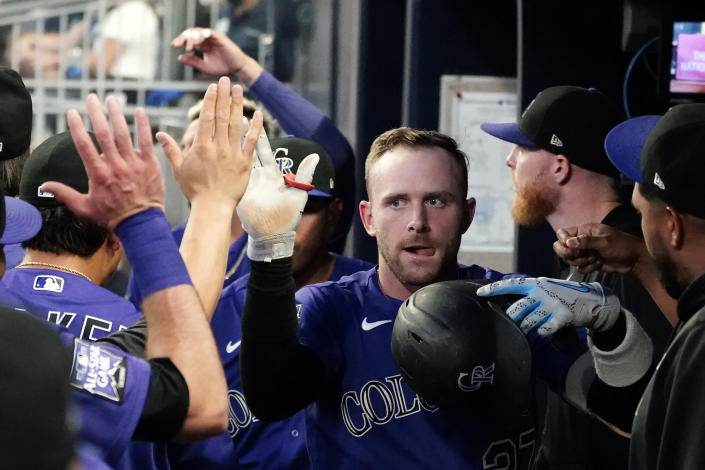 Colorado Rockies shortstop Trevor Story celebrates in the dugout after hitting a solo home run in the first inning of a baseball game against the Atlanta Braves Tuesday, Sept. 14, 2021, in Atlanta. (AP Photo/John Bazemore)