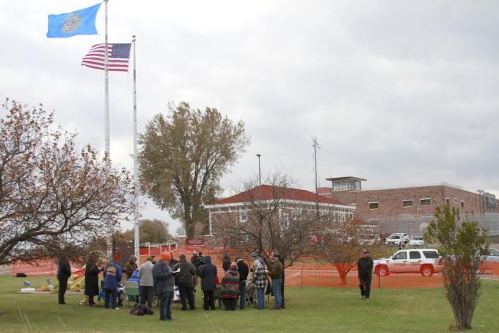 Protesters pray and sing outside the South Dakota State Penitentiary in Sioux Falls, Monday, Nov. 4, 2019, where Charles Russell Rhines is scheduled to die Monday, by lethal injection for the death of a former co-worker. Officials are waiting to hear from the United States Supreme Court on three appeals filed by Rhines. The state attorney general's office said it will not proceed with the execution until the Supreme Court rules on the matter. (AP Photo/Stephen Groves)