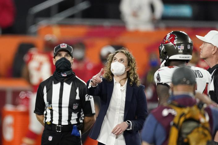 A health care worker tosses the coin before the NFL Super Bowl 55 football game between the Tampa Bay Buccaneers and the Kansas City Chiefs, Sunday, Feb. 7, 2021, in Tampa, Fla. (AP Photo/Ashley Landis)