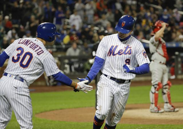 New York Mets' Michael Conforto, left, celebrates with Brandon Nimmo after Nimmo scored on a double by Pete Alonso as Philadelphia Phillies catcher J.T. Realmuto , back right, reacts during the third inning of a baseball game Monday, April 22, 2019, in New York. (AP Photo/Frank Franklin II)