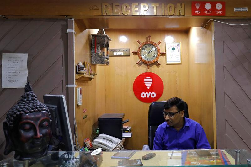 An employee sits next to the logo of OYO, India's largest and fastest-growing hotel chain, at the reception of a hotel in New Delhi