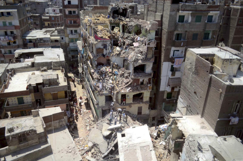 Rescue workers look for survivors buried under debris of damaged buildings following the collapse of an 11-story building under construction onto three adjacent buildings that killed at least 10 people in the Gomrouk neighborhood of Alexandria, Egypt, July 15, 2012. With real estate at a premium in big cities like Alexandria and Cairo, developers seeking bigger profits frequently violate planning permits and exceed the number of stories allowed. (AP Photo/Tarek Fawzy)