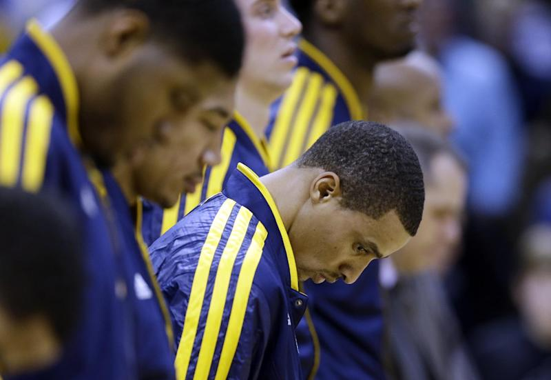 Indiana Pacers' George Hill pauses during a moment of silence for those who were killed and injured in the Connecticut elementary school shooting before an NBA basketball game against the Philadelphia 76ers, Friday, Dec. 14, 2012, in Indianapolis. (AP Photo/Darron Cummings)