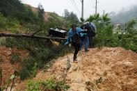 Men cross a mudslide blocking a road after the passage of Storm Eta, in Purulha