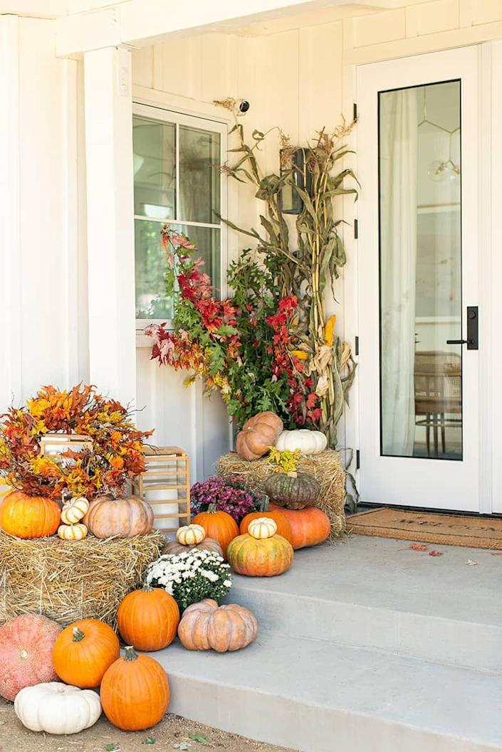 """<p>Lined with traditional fall favorites like corn stalks and hay bales, this eye-catching, pumpkin-themed front porch is proof that, sometimes, more is more.</p><p><strong>Get the tutorial at <a href=""""https://sugarandcharm.com/fall-porch"""" rel=""""nofollow noopener"""" target=""""_blank"""" data-ylk=""""slk:Sugar & Charm"""" class=""""link rapid-noclick-resp"""">Sugar & Charm</a>.</strong></p><p><a class=""""link rapid-noclick-resp"""" href=""""https://go.redirectingat.com?id=74968X1596630&url=https%3A%2F%2Fwww.walmart.com%2Fsearch%2F%3Fquery%3Dcraft%2Bleaves&sref=https%3A%2F%2Fwww.thepioneerwoman.com%2Fhome-lifestyle%2Fdecorating-ideas%2Fg36732301%2Foutdoor-fall-decorations%2F"""" rel=""""nofollow noopener"""" target=""""_blank"""" data-ylk=""""slk:SHOP CRAFT LEAVES"""">SHOP CRAFT LEAVES</a></p>"""