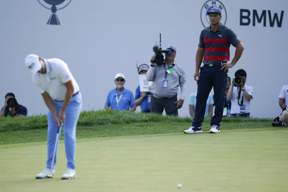Bryson DeChambeau, right, watches as Patrick Cantlay putts on the 16th green during the final round of the BMW Championship golf tournament, Sunday, Aug. 29, 2021, at Caves Valley Golf Club in Owings Mills, Md. (AP Photo/Julio Cortez)