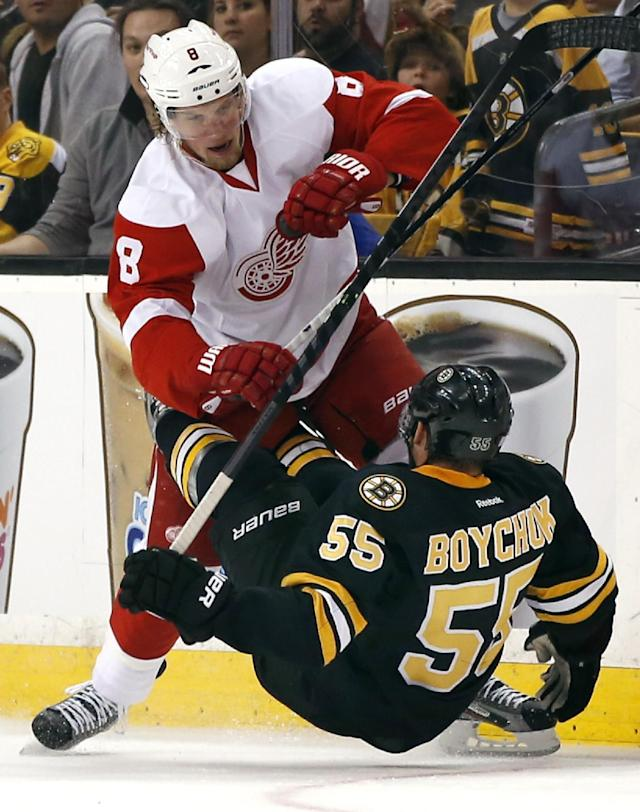 Detroit Red Wings left wing Justin Abdelkader (8) checks Boston Bruins defenseman Johnny Boychuk (55) to the ice in the first period of an NHL hockey game in Boston, Monday, Oct. 14, 2013. (AP Photo/Elise Amendola)