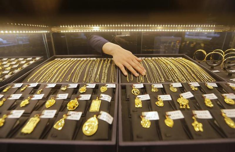 An employee arranges gold jewellery in the counter of a gold shop in Wuhan, Hubei province April 16, 2013. REUTERS/Stringer/Files