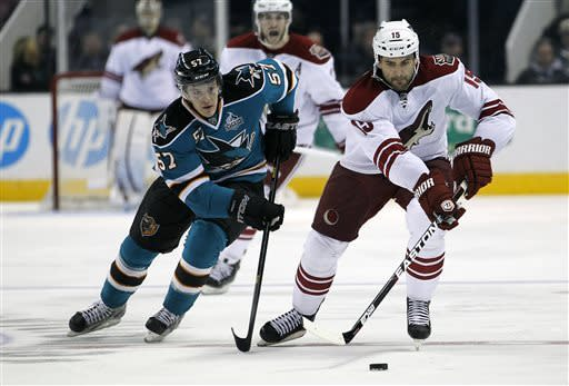 San Jose Sharks center Tommy Wingels (57) chases Phoenix Coyotes center Boyd Gordon (15) with the puck during the second period of an NHL hockey game in San Jose, Calif., Saturday, March 30, 2013. (AP Photo/Tony Avelar)