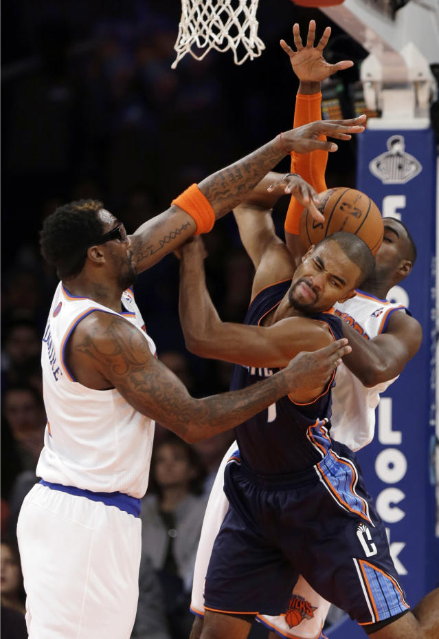 New York Knicks' Amar'e Stoudemire, left, and Tim Hardaway Jr., back right, defend against Charlotte Bobcats' Ramon Sessions, front right, during the first half of an NBA basketball game on Friday, Oct. 25, 2013, in New York. (AP Photo/Frank Franklin II)