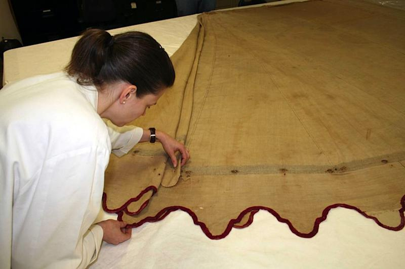 In this March 2013 photo provided by the Museum of the American Revolution, Michelle Presnall examines the tent George Washington used as his residence and command center during the Revolutionary War, near Philadelphia.   The tent is being duplicated down to the finest stitch and will serve as an education tool and goodwill ambassador for a new museum coming to the city's historic district. The 22-feet-long, 15-feet-wide oval tent, also called a marquee, is being reproduced this summer as part of a new partnership between the planned Museum of the American Revolution and Colonial Williamsburg.  (AP Photo/Museum of the American Revolution)