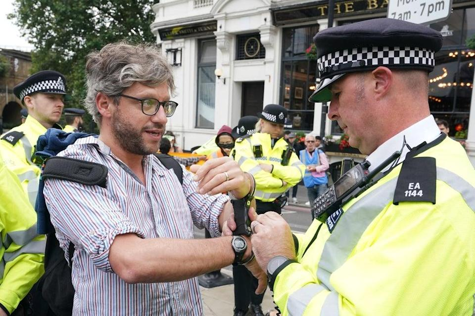 Police detain a man after he glued himself to the road during the protest (Ian West/PA) (PA Wire)